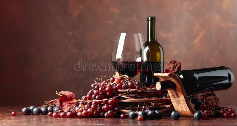 Red wine and fresh grapes with dried up vine leaves. stock image
