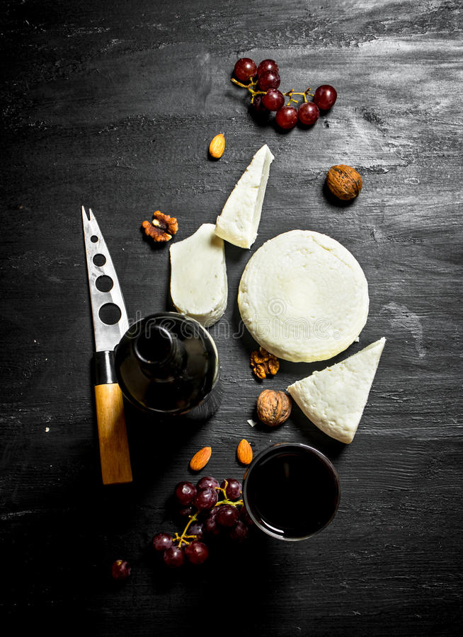 Red wine with fresh sheep cheese and grapes. On a black wooden background royalty free stock photos