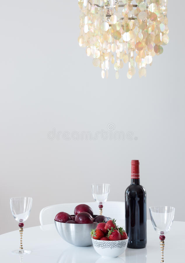 Red wine with fruits on a table, and beautiful chandelier stock photography