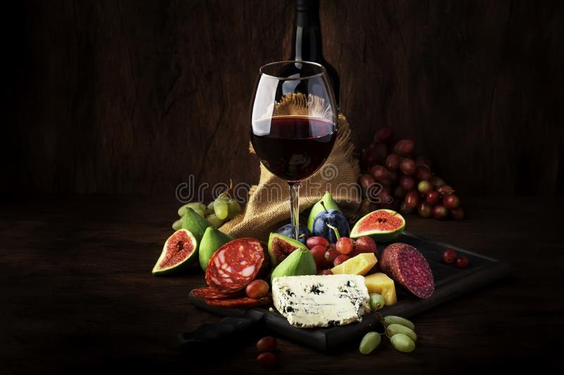 Red wine glass and appetizers, cheese, salami, figs, grapes, vintage wooden table background, selective focus, copy space. Red wine glass and appetizers, cheese stock photo