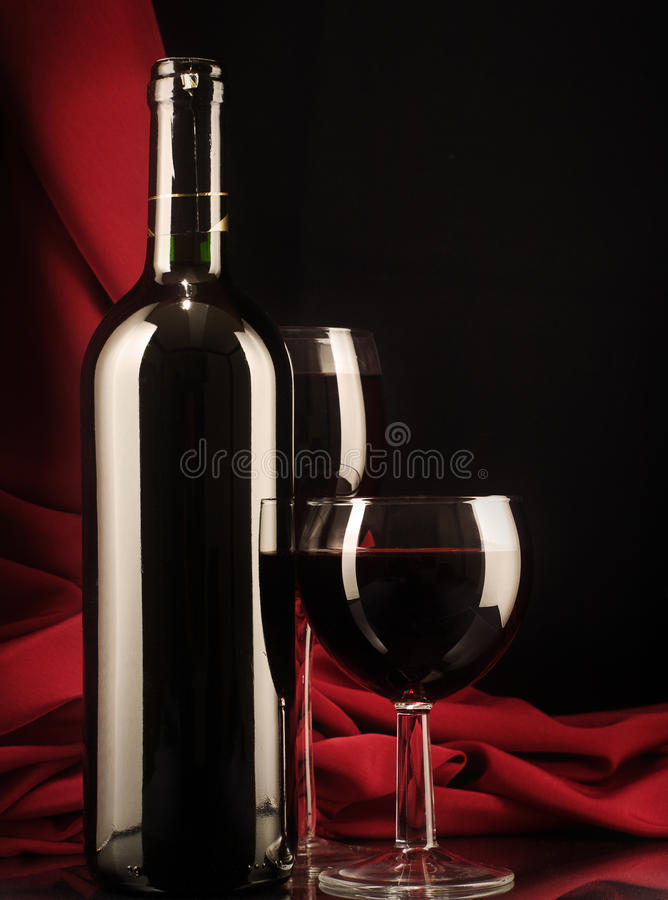 Red wine glass and bottle on a silk background. Low key still life. Red wine glass and bottle on a silk background royalty free stock photo