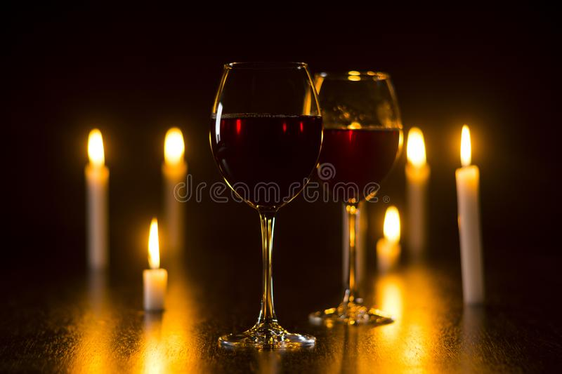 Red wine glass and candle romantic ambiance composition photography stock images
