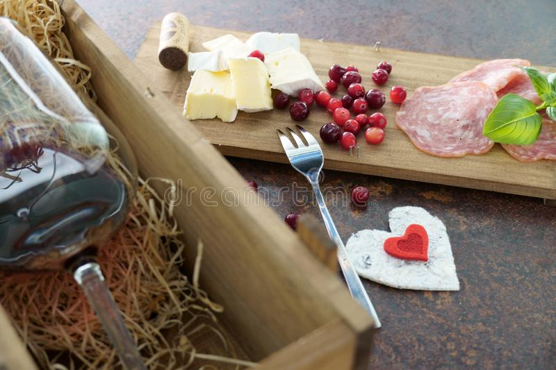 Red wine glass with cheese and salami in wooden box on concrete table stock images