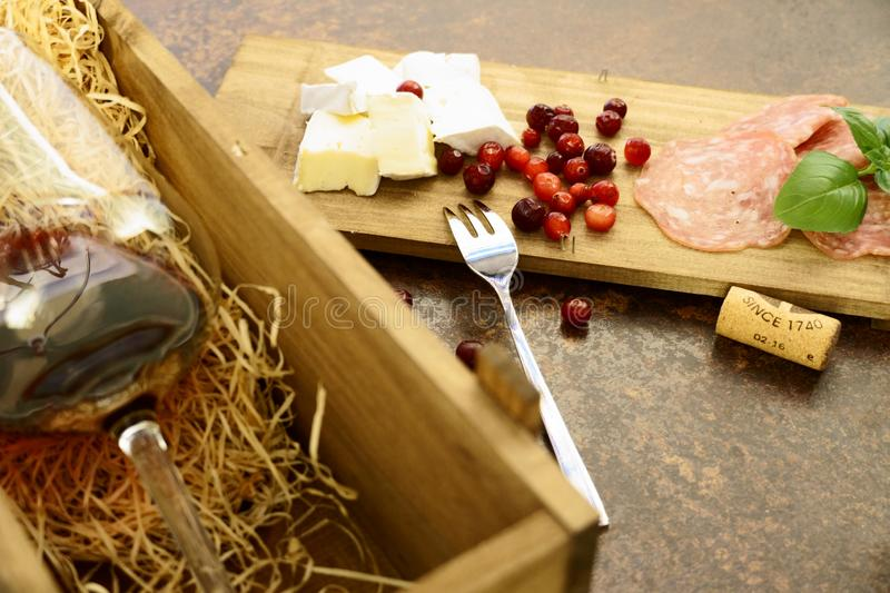 Red wine glass with cheese and salami in wooden box on concrete table stock photo
