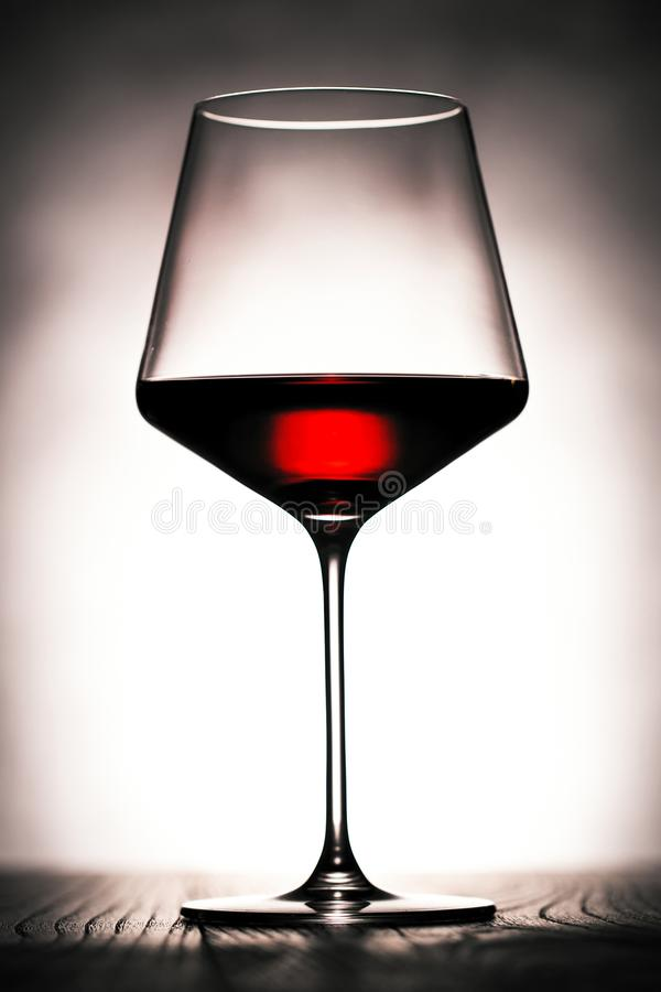 Red wine glass on dark wooden Table. stock photos