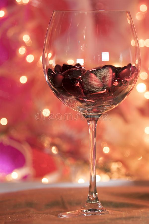 Red wine glass filled with red valentine romantic hearts for a toast stock photography