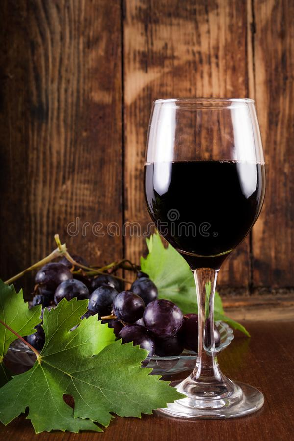 Red Wine In Glass And Grape On Plate With Vine Decoration