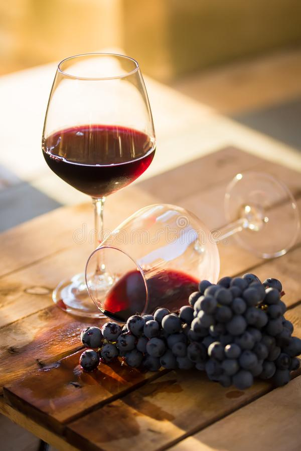 Red wine in a glass, overturned glass of wine, wine flowing, concept of drunkenness or fail. Dropped wine glass and spilled red wine on a wooden table with one stock photos