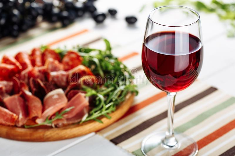 Red wine glass with sliced jamon plate on table background. Horizontal close-up view royalty free stock photography