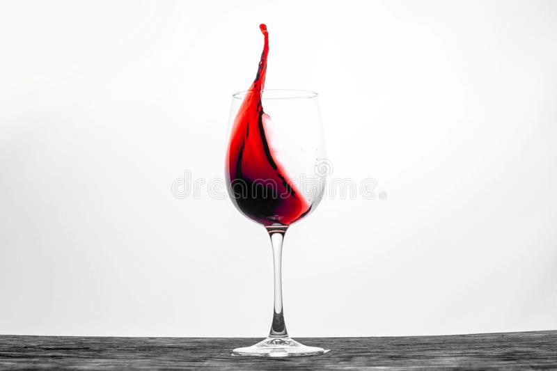 Red wine in the glass splashes in motion on a white background. Stylish design card stock photography