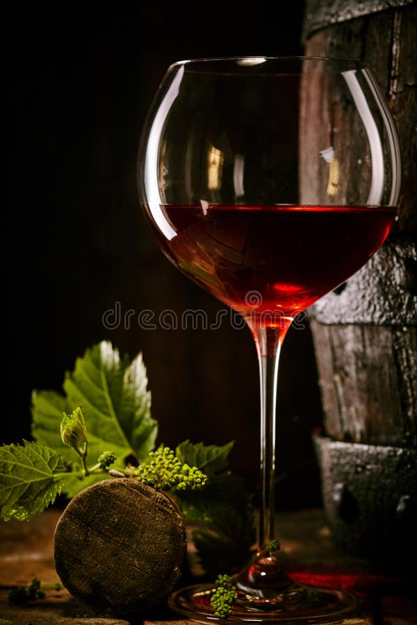 Red wine in a glass with vine leaves and cork. Alongside an old oak cask in a shadowy cellar in a conceptual image of viticulture and alcohol royalty free stock images
