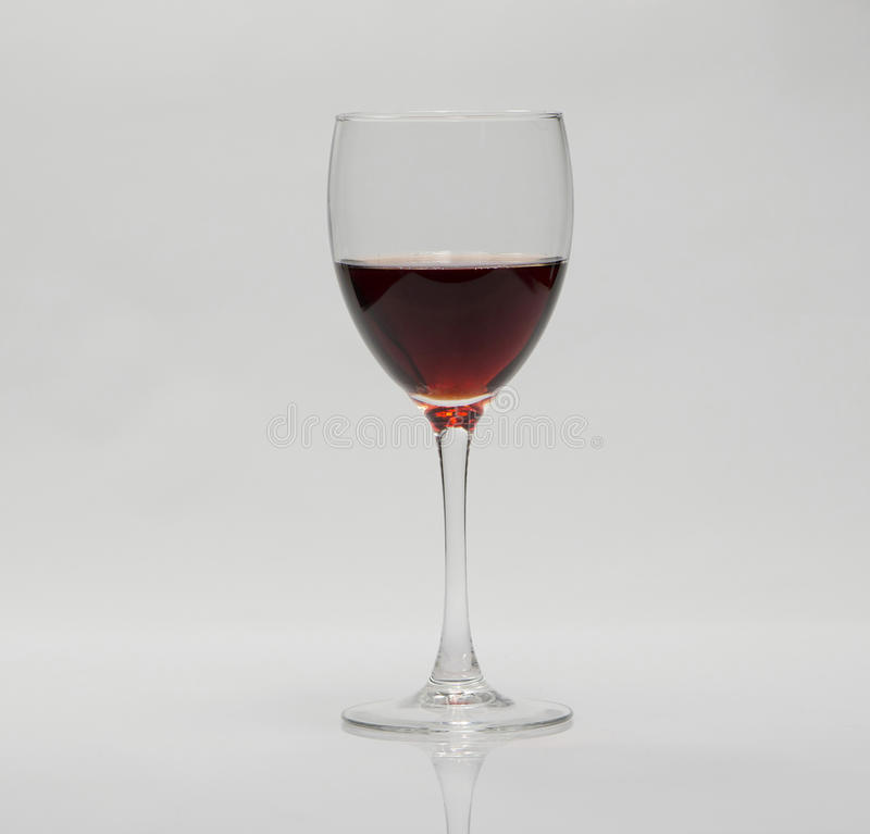 Red wine. In a glass on a white table stock images