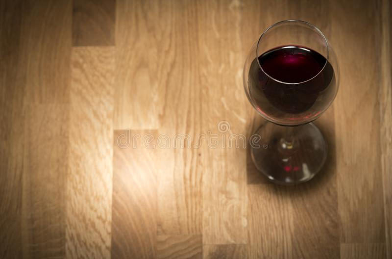 Red wine in a glass. On a wooden table stock image