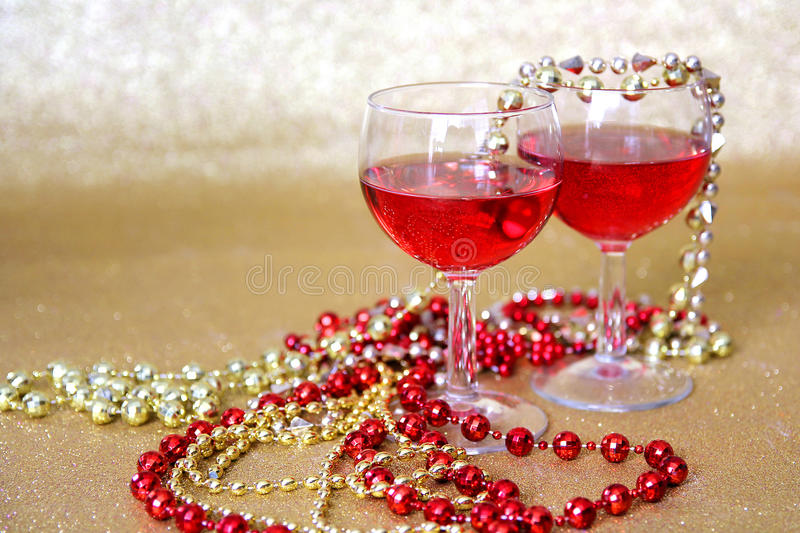 Red Wine Glasses and Bead Decorations in with Gold Background. Two wine glasses filled with a red drink are surrounded by bright beaded New Years Eve necklaces royalty free stock photo