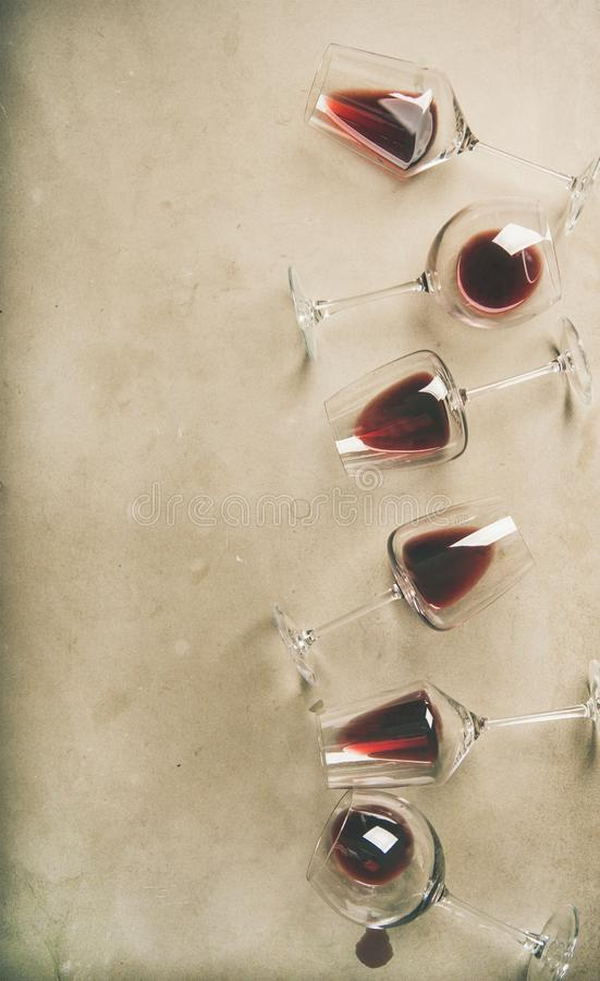 Red wine in glasses over grey concrete background, vertical composition. Flat-lay of red wine in glasses over grey concrete background, top view, copy space stock images