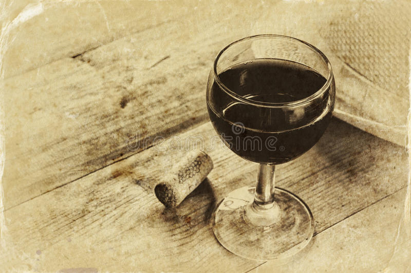 Red wine glasson wooden table. vintage filtered image. black and white style photo. Red wine glass on wooden table. vintage filtered image. black and white style royalty free stock photo