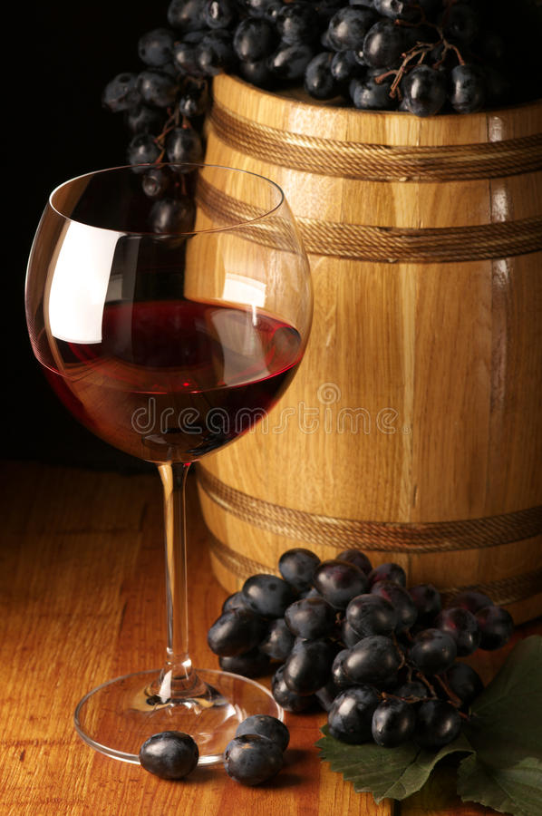 Red wine, grape and barrel. Glass of red wine, dark grape and souvenir barrel on wooden surface stock image