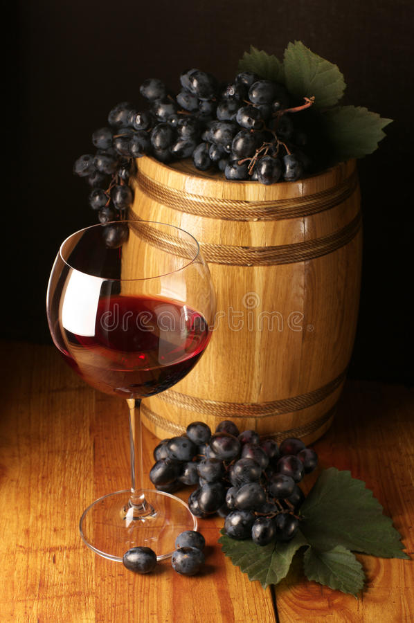 Red wine, grape and barrel. Glass of red wine, dark grape and souvenir barrel on wooden surface stock photo