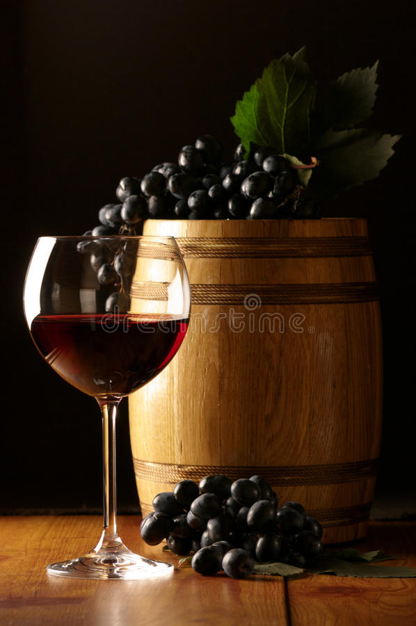 Red wine, grape and barrel. Glass of red wine, dark grape and souvenir barrel on wooden surface stock photos