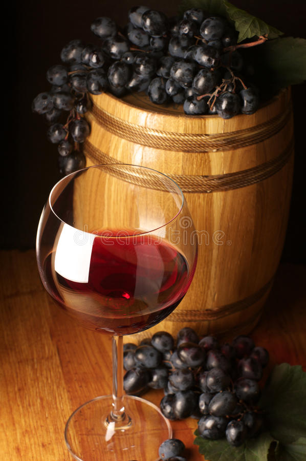 Red wine, grape and barrel. Glass of red wine, dark grape and souvenir barrel on wooden surface royalty free stock photography