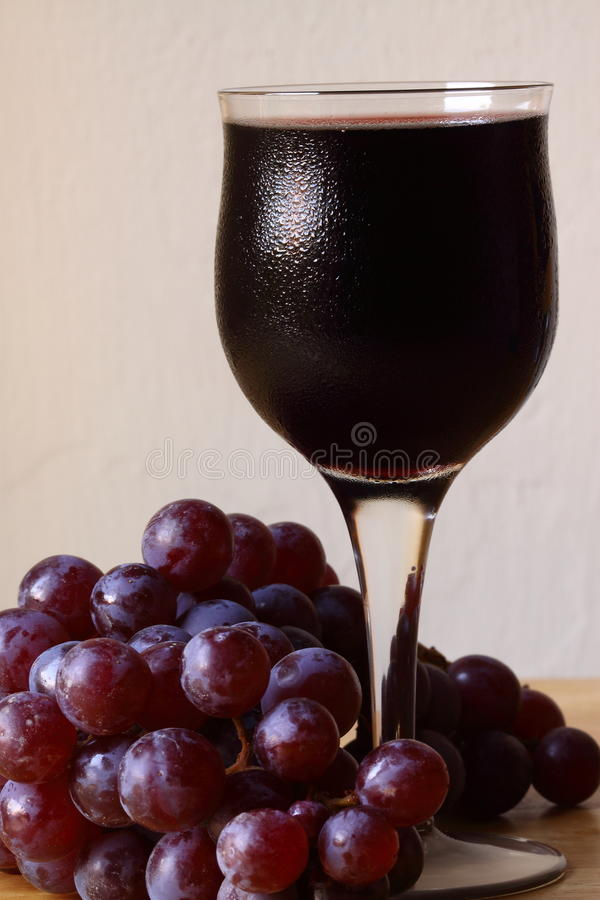 Red wine with grapes. Photograph of a glass of red wine with grapes on a table stock images