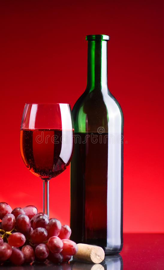 Red wine and grapes. A bottle of red wine besides a glass of red wine and wine grapes royalty free stock photos