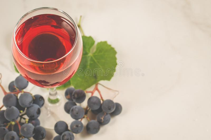 red wine and grapes/Glass of red wine and grapes on a white marble background. Top view stock photo