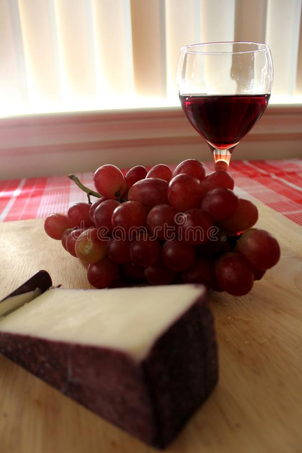 Red wine, grapes and wine washed cheese. Wine, grapes and cheese on a wood cutting board. Table with red and white buffalo check tablecloth. Late afternoon royalty free stock photo