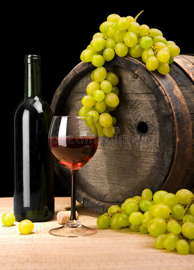 Red wine and green grape and barrel. Dark composition red wine in glass and bottle and green grape on a background of old wine barrel royalty free stock photography