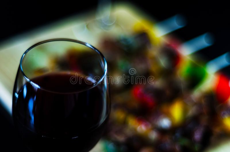 Red wine and grilled skewers of meat and vegetables on a wooden stock images