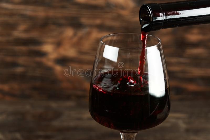 In a glass pour red wine stock image