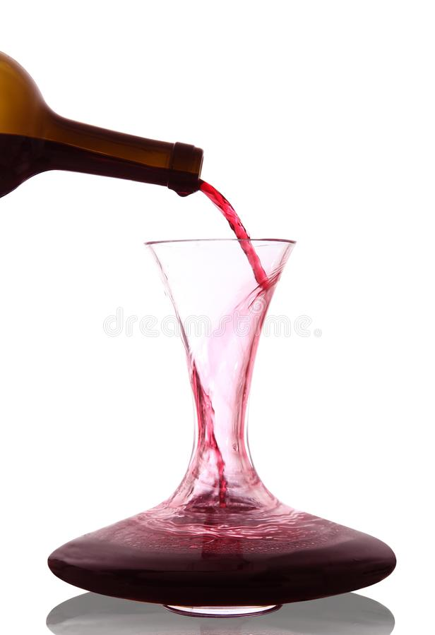 Red wine poured into decanter. On white background royalty free stock images