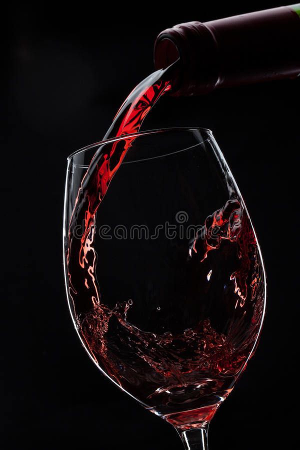 Red wine poured into glass royalty free stock photo