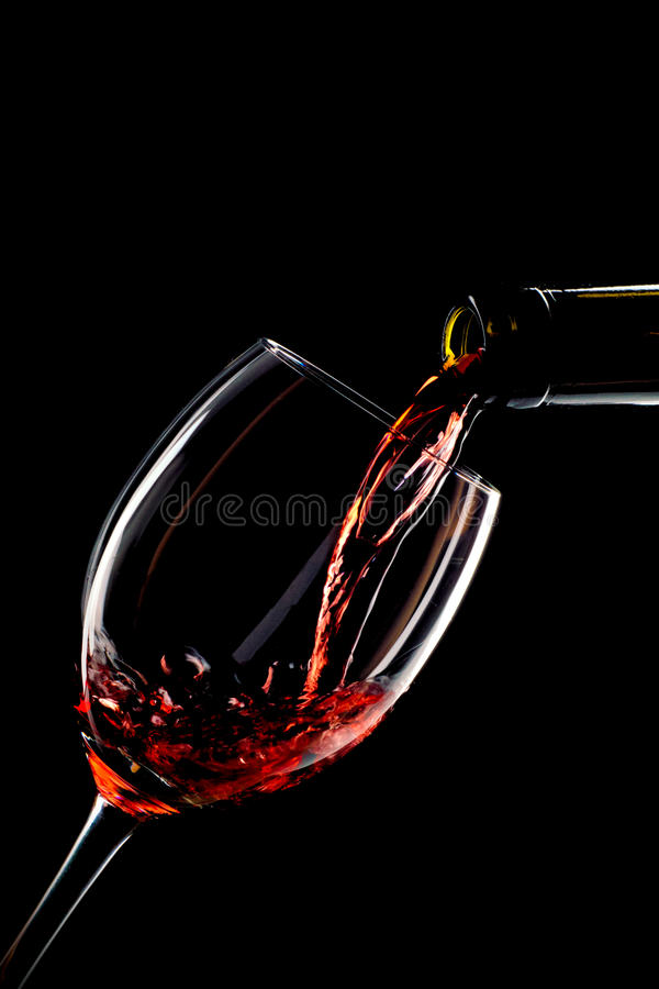 Red wine poured into a glass. On black background royalty free stock photo