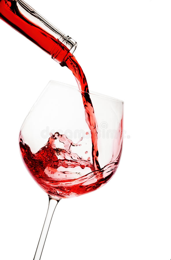 Red wine poured in a glass. Isolated on white stock photos