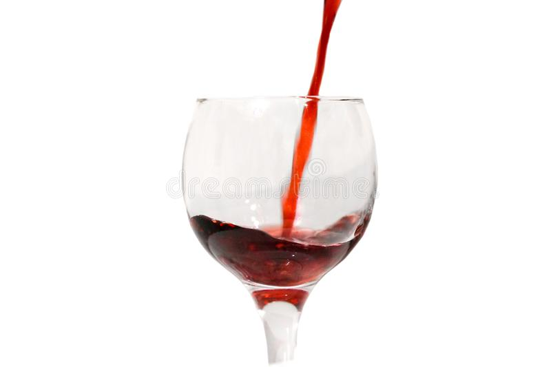 Red wine is poured into a glass, waves, isolate. Red ruby wine poured vertically down into a glass wine glass, splashing wine, isolate on a white royalty free stock images