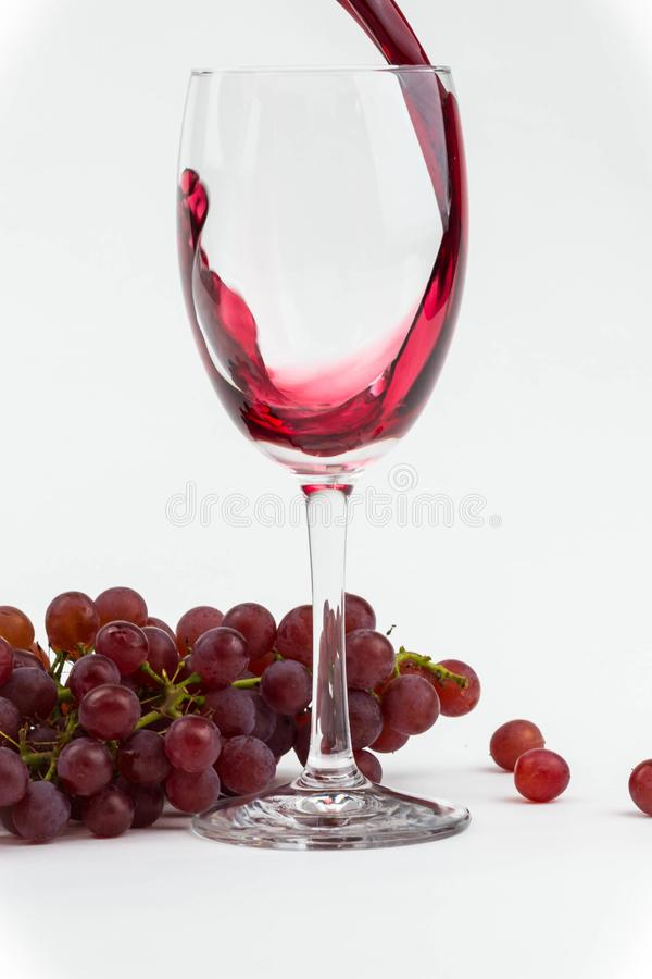 Red wine poured into a wineglass with fresh grapes as background. Isolated photo. royalty free stock photos