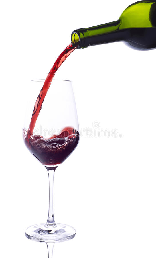 Red wine pouring from bottle. To glass stock images