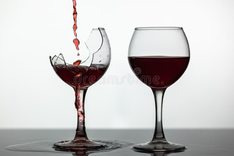 Red wine pouring into broken wine glass on the wet surface. Rose wine pour royalty free stock photography