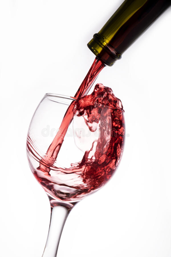 Red wine pouring into the glass from bottle isolated on white background stock photos