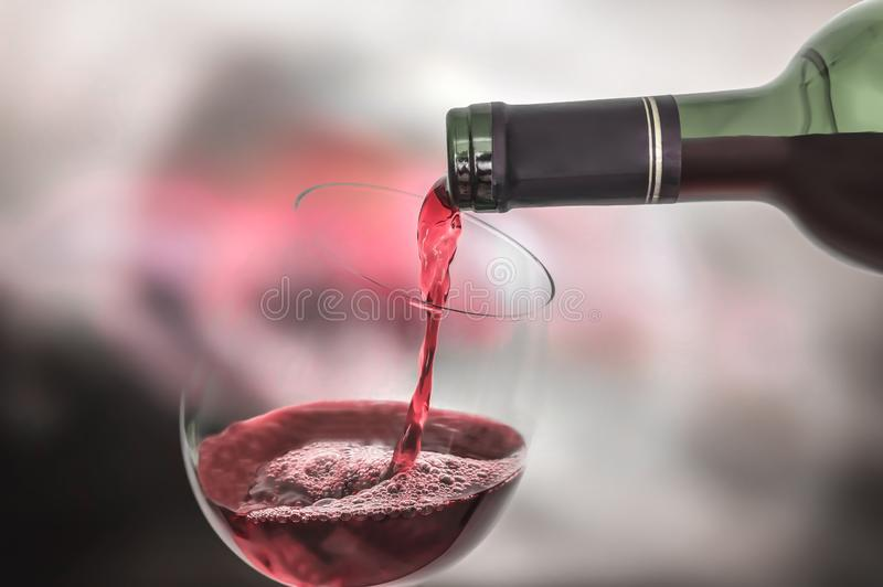 Red wine pouring into a wine glass. Celebration concept stock photography