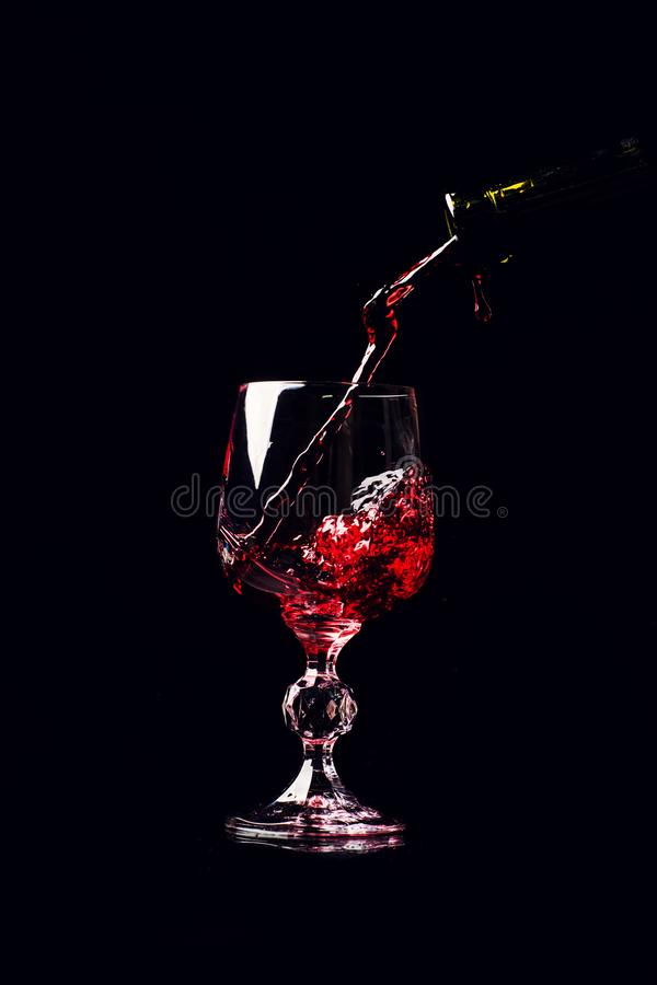 Red wine pouring into wine glass with splash, isolated on black stock images