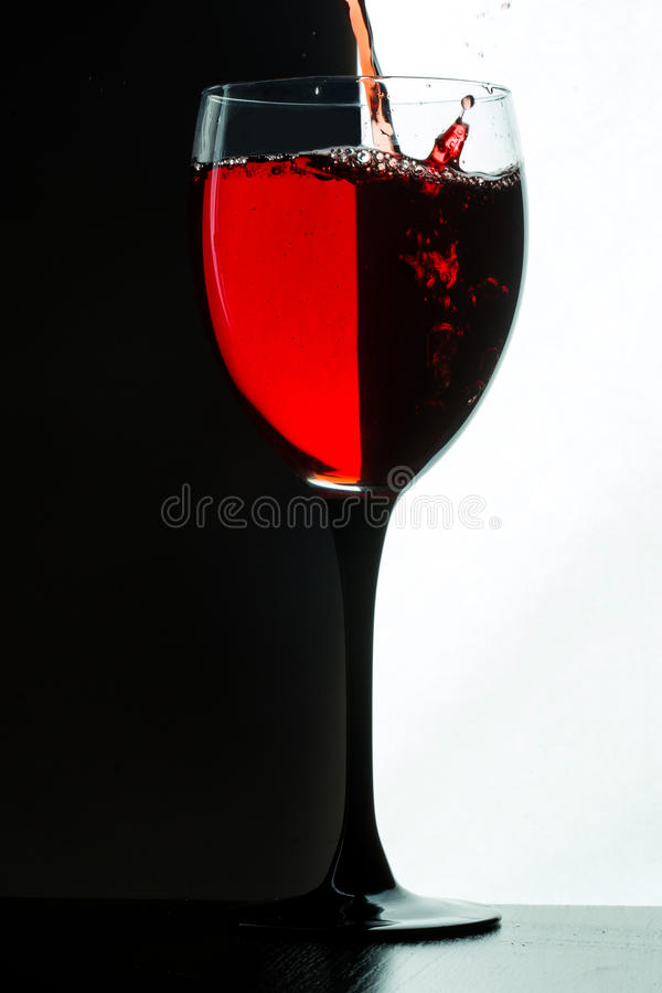 Red wine pouring. white on black background royalty free stock image