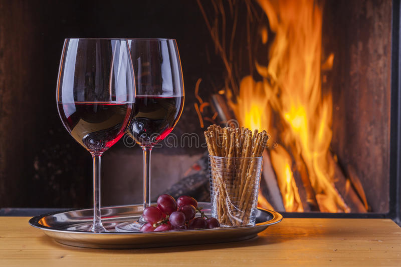 Red wine with snacks and grapes at fireplace royalty free stock image