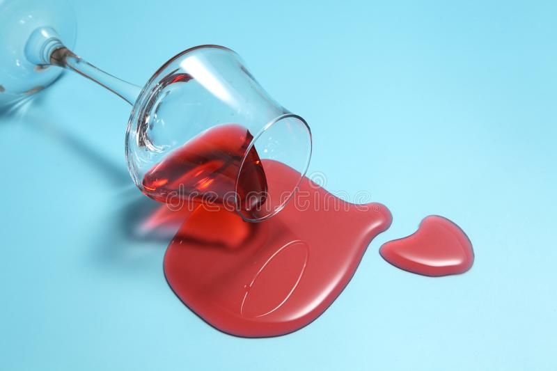 Red wine spilled from glass over blue background with a blank space for a text stock photo