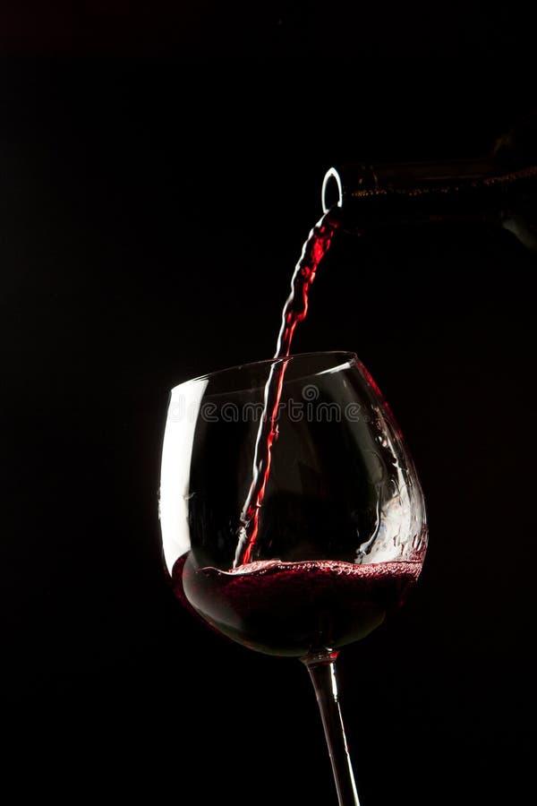 Red wine splash on a glass stock photo