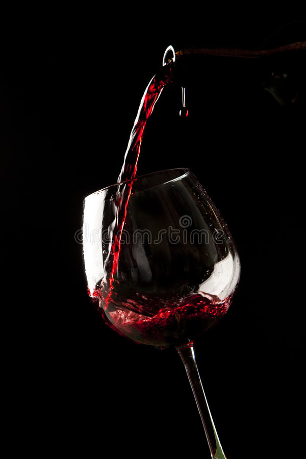 Red wine splash on a glass stock photography