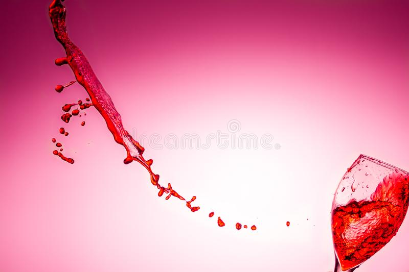 Red wine splashing out of falling glass on bright pink background with copy space royalty free stock photos
