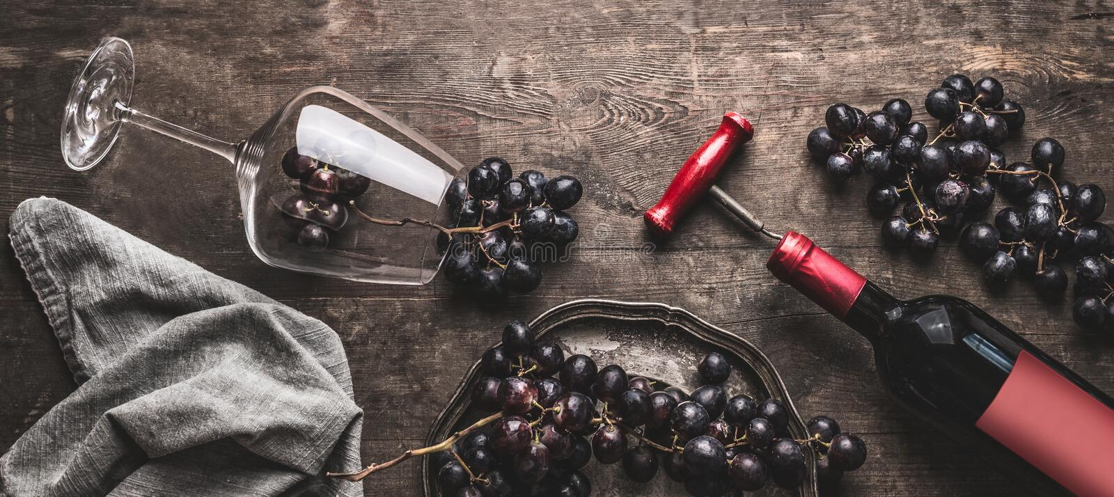 Red wine still life with bottle and vintage corkscrew, glass and grapes on aged wooden background royalty free stock photos