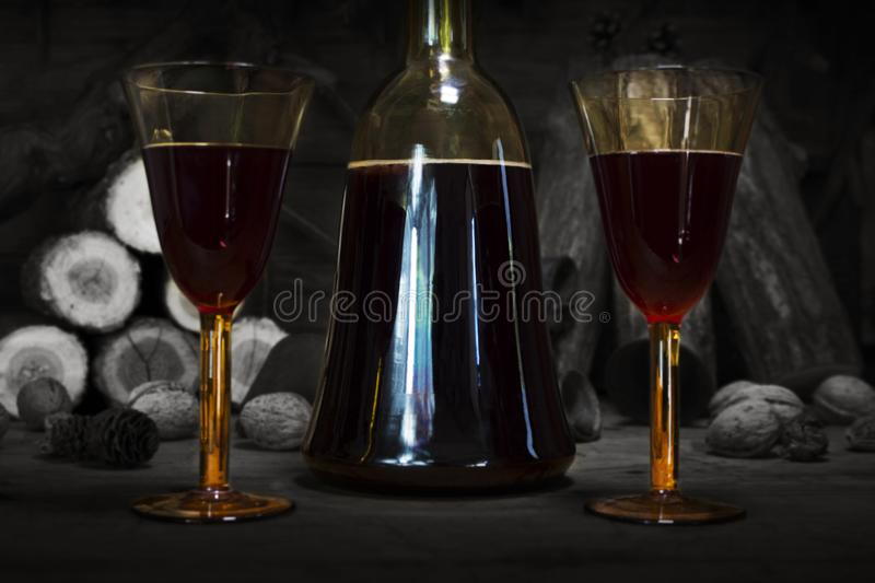Red Wine Vintage Bottle and Glasses Resting On Wooden Table Against Christmas Background With Wood logs and Pine Branches royalty free stock image